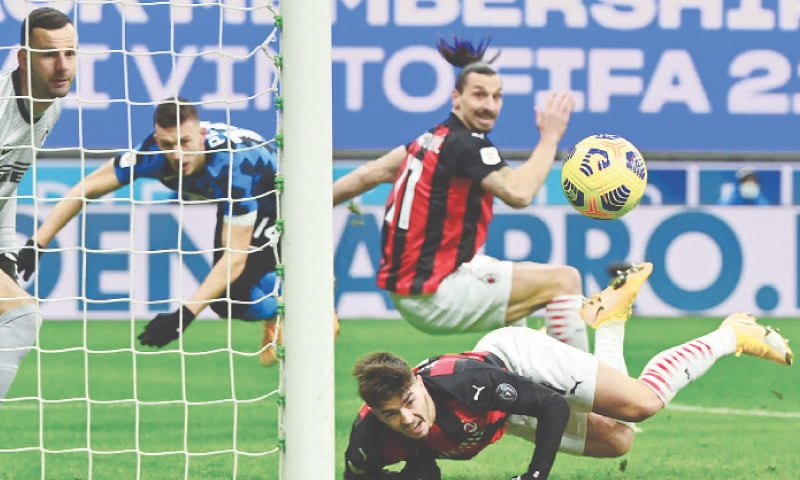 MILAN: AC Milan's Brahim Diaz (bottom) heads the ball over team-mate Zlatan Ibrahimovic during the Coppa Italia quarter-final against Inter Milan at the San Siro.—AFP