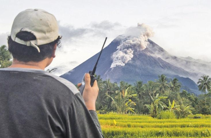 A VOLUNTEER uses his walkie talkie while monitoring Mount Merapi during an eruption.—AP