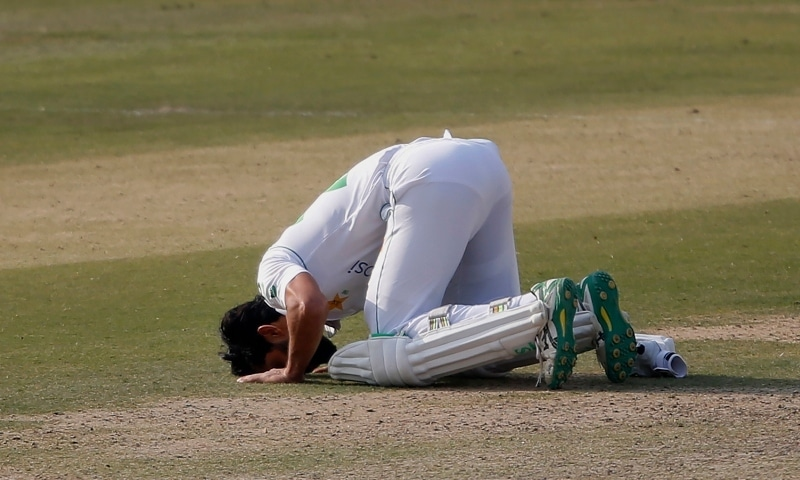 Fawad Alam kisses the ground after scoring a century during the second day of the first cricket test match between Pakistan and South Africa at the National Stadium on Jan 27. — AP