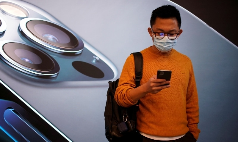 In this 2020 file photo, a man wears a face mask while waiting at an Apple Store before Apple's 5G new iPhone 12 go on sale. — Reuters