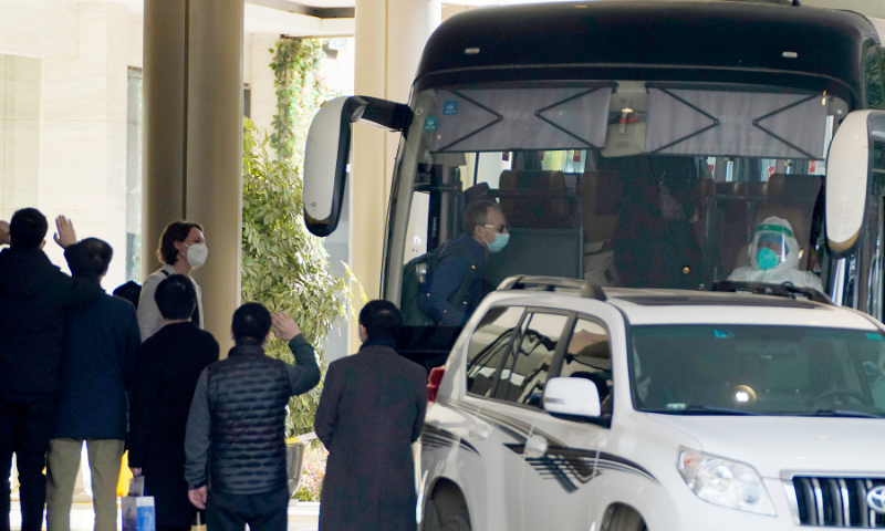 Workers wave to the team of experts from the World Health Organisation who ended their quarantine and prepare to leave the quarantine hotel by bus in Wuhan in central China's Hubei province on Thursday. — AP