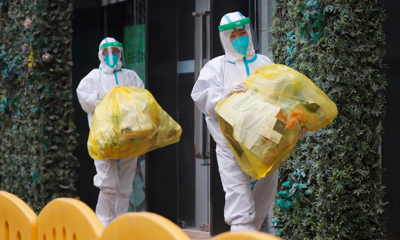 People in protective suits walk outside the hotel where members of the World Health Organisation (WHO) team tasked with investigating the origins of the coronavirus pandemic are quarantined, in Wuhan, Hubei province, China  on Jan 28. — Reuters