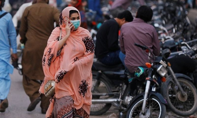 A woman wears a protective mask while walking along a road in Karachi on Dec 2. — Reuters/File