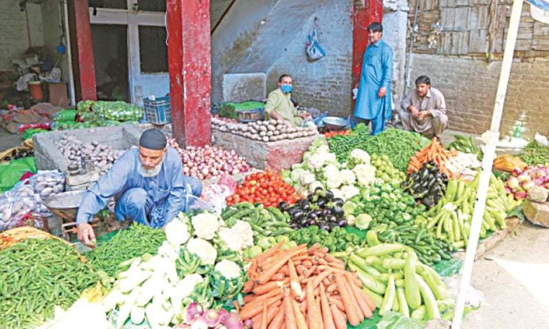 In this file photo, vendors await customers in vegetable market in Mingora. — Dawn