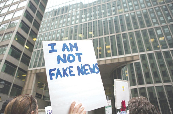 A protester holds an 'I am not fake news' sign | AFP