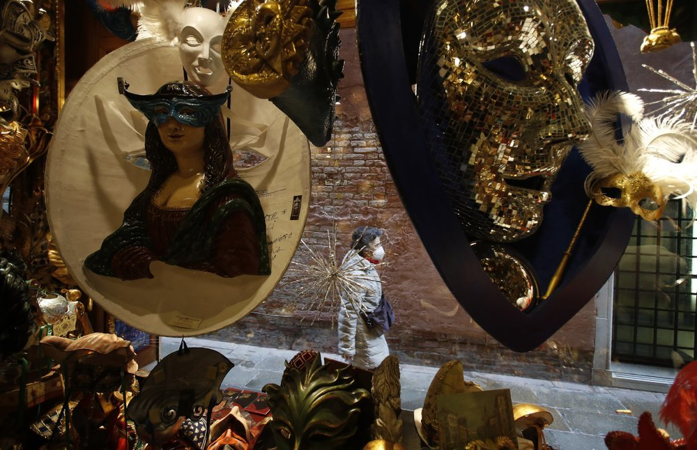 A woman wearing a sanitary mask walks next to a carnival masks shop in Venice, Italy.