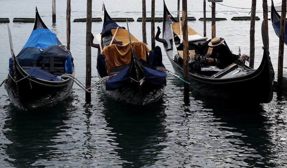 A Gondolier sits in his Gondola docked in St Mark's square in Venice.