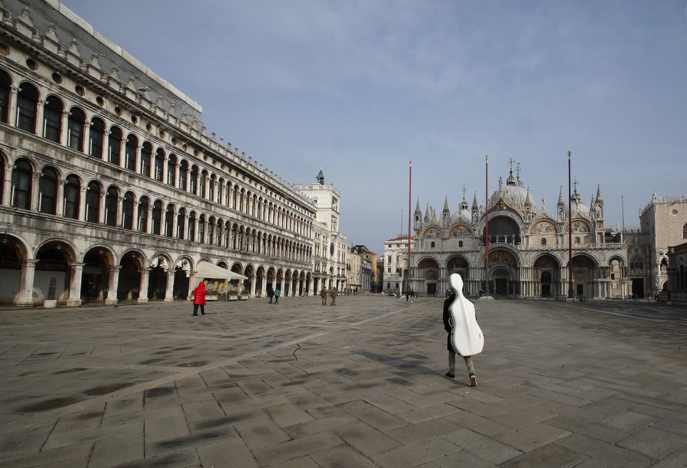 A young man walks in an empty St Mark's Square in Venice.