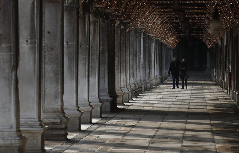 People walk down a passageway near St Mark's Square in Venice.