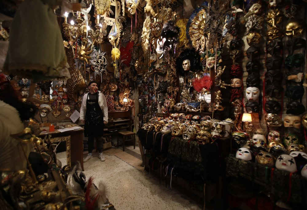 Carnival masks placed on display in a Venetian artisan mask makers workshop.