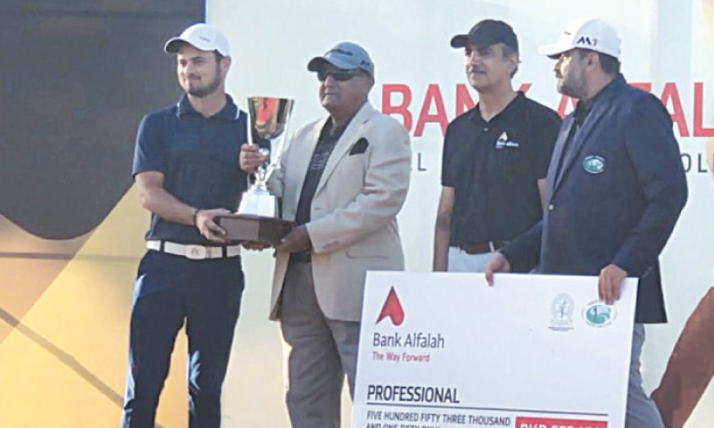 KARACHI: Ahmed Baig receives the trophy after winning the DHA Karachi Cup on Sunday.