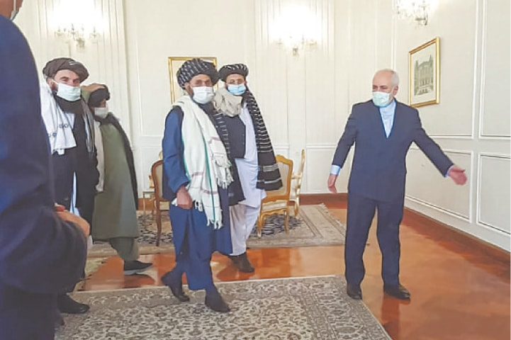 IRAN'S Foreign Minister Mohammad Javad Zarif (right) greets Taliban leader Mullah Abdul Ghani Baradar (centre) on Sunday.—AFP