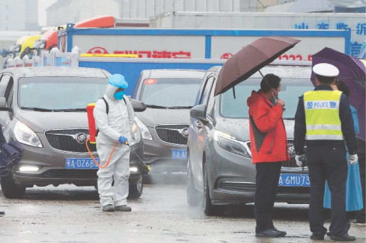 A WORKER disinfects a vehicle from the World Health Organisation's convoy while they were visiting the wholesale market.—AP