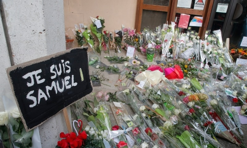 """In this Oct.17, 2020 file photo, a poster reading """"I am Samuel"""" and flowers lay outside the school where slain history teacher Samuel Paty was working, in Conflans-Sainte-Honorine, northwest of Paris. — AP"""