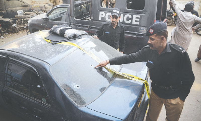 A policeman points to a bullet hole on the ill-fated vehicle on Tuesday.—Shakil Adil/White Star