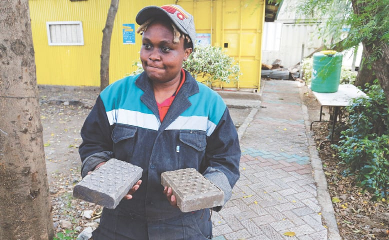 Nzambi Matee, the founder of Kenya's Gjenge Makers, a social enterprise that recycles and up-cycles waste plastic into construction products such as paving bricks, shows pavers to the media at an event on Tuesday.—Reuters