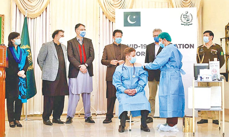 ISLAMABAD: Prime Minister Imran Khan looks on as the first Covid-19 vaccine is administered to a doctor on Tuesday.—APP