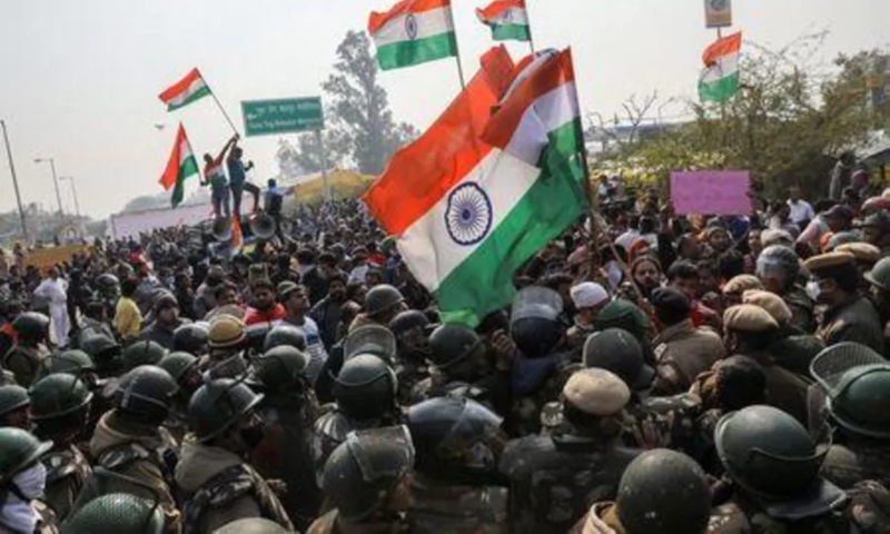 People shout anti-farmers slogans and wave India's flags as police officers try to stop them, at a site of the protest against farm laws at Singhu border near New Delhi, India, January 29. — Reuters