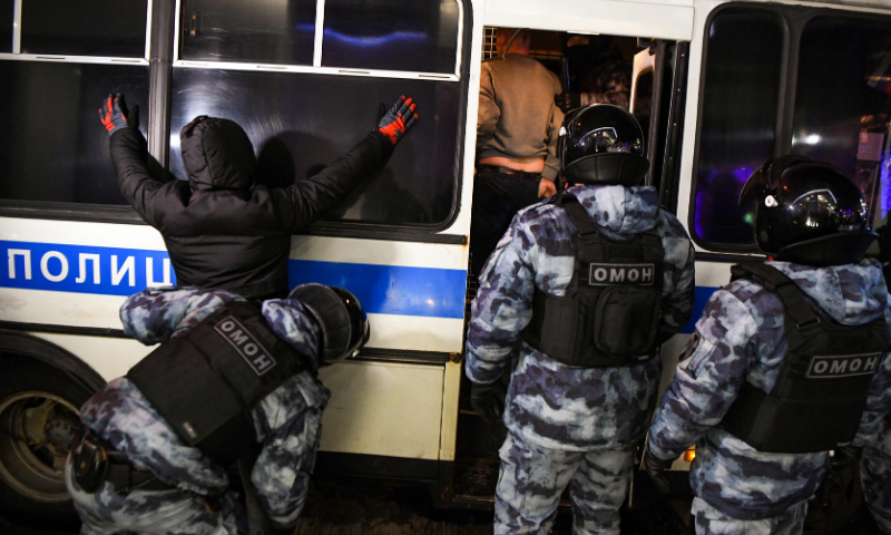 A riot police officer searches a detained man during a protest against a court ruling ordered Russian opposition leader Alexei Navalny jailed for nearly three years, in downtown Moscow early on February 3. — AFP