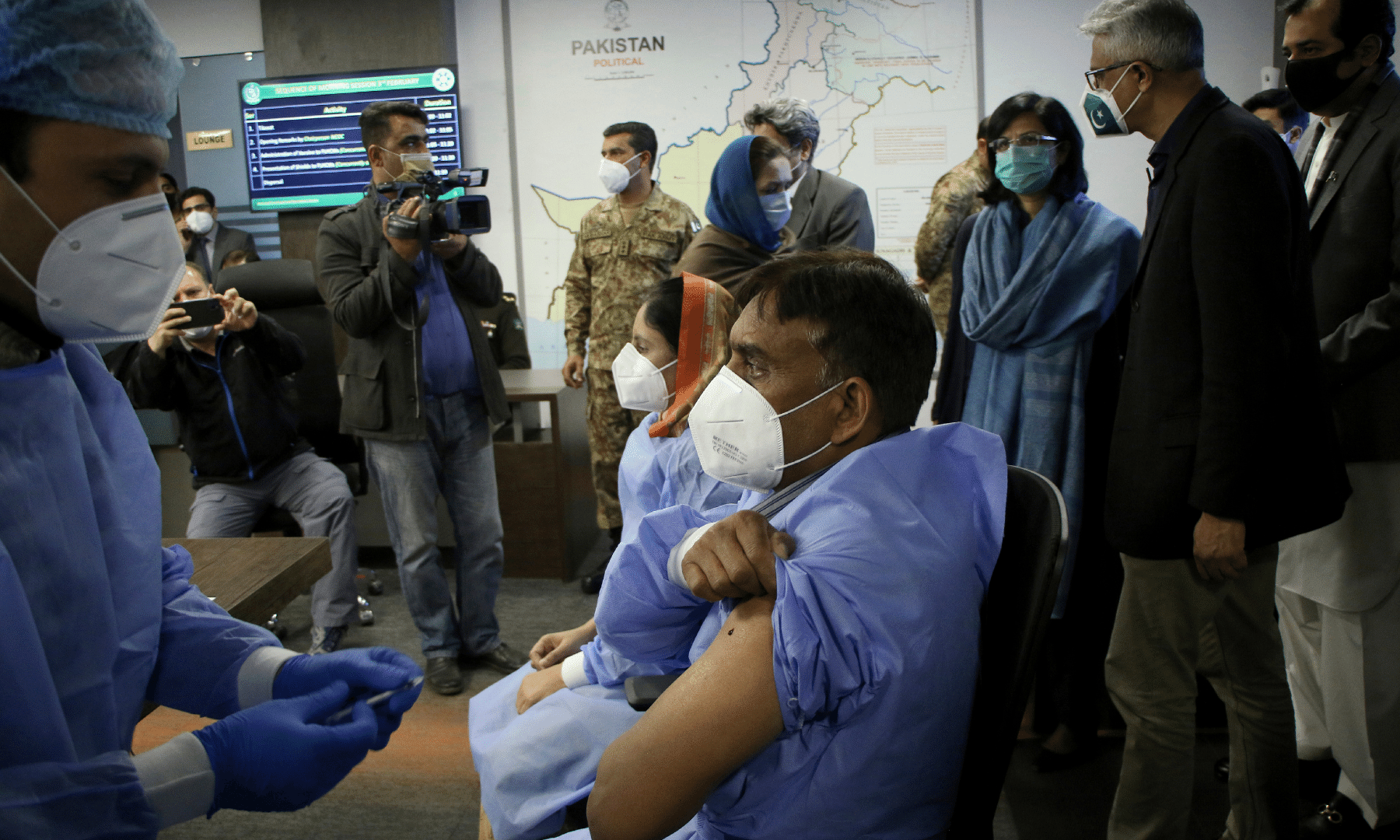 A health worker administers the Chinese Sinopharm Covid-19 vaccine to his colleague while Prime Minister's advisor on health Dr Faisal Sultan, second right, and other officials watch during a ceremony to start the vaccination campaign in Islamabad. — AP