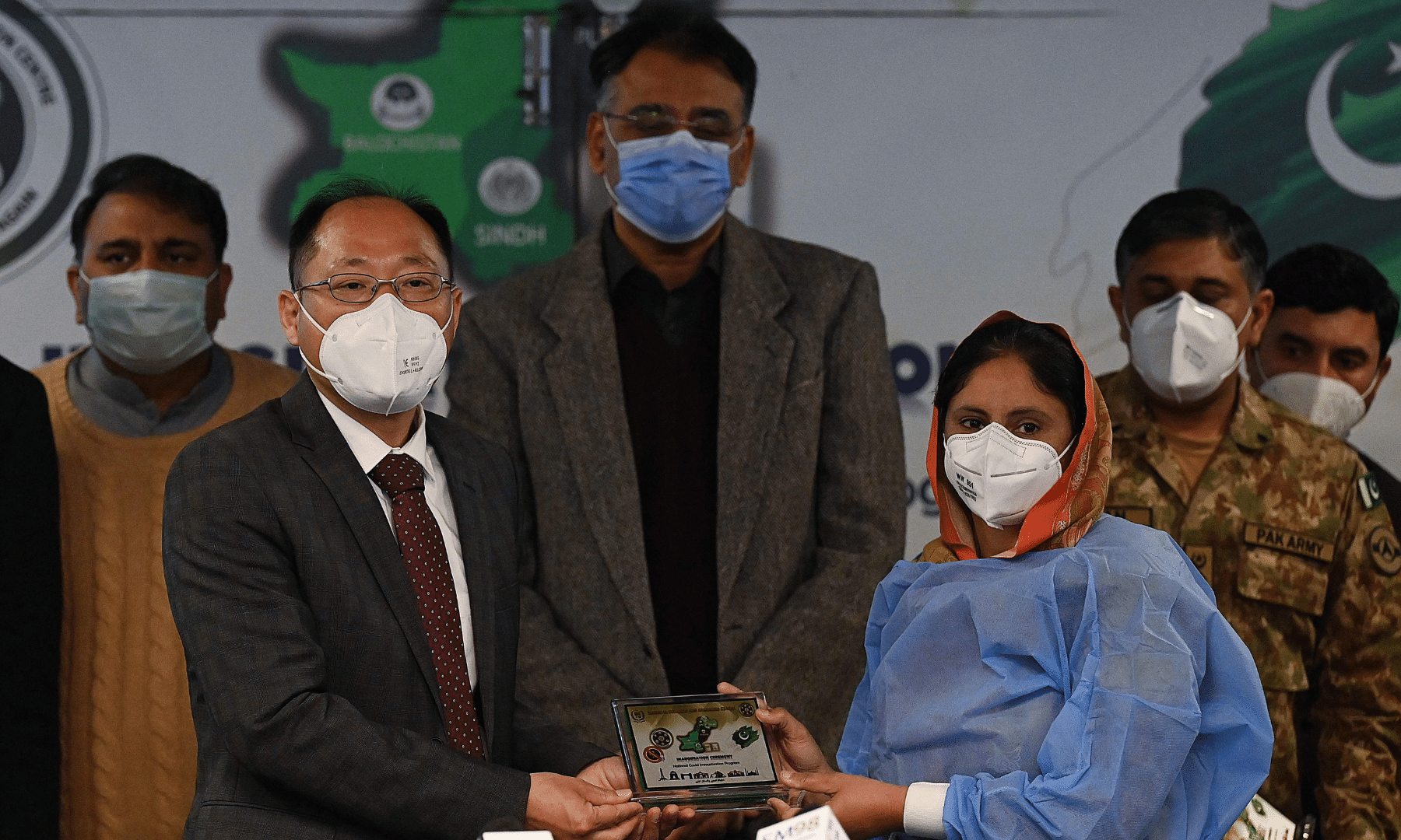 Chief guest, Commercial Minister Counsellor China Xie Guoxiang (L) gives a souvenir to a health worker after she received a dose of the Chinese-made Sinopharm Covid-19 vaccine, as the head of National Command and Operation Centre Asad Umar (C) looks on, in Islamabad on Wednesday. — AFP