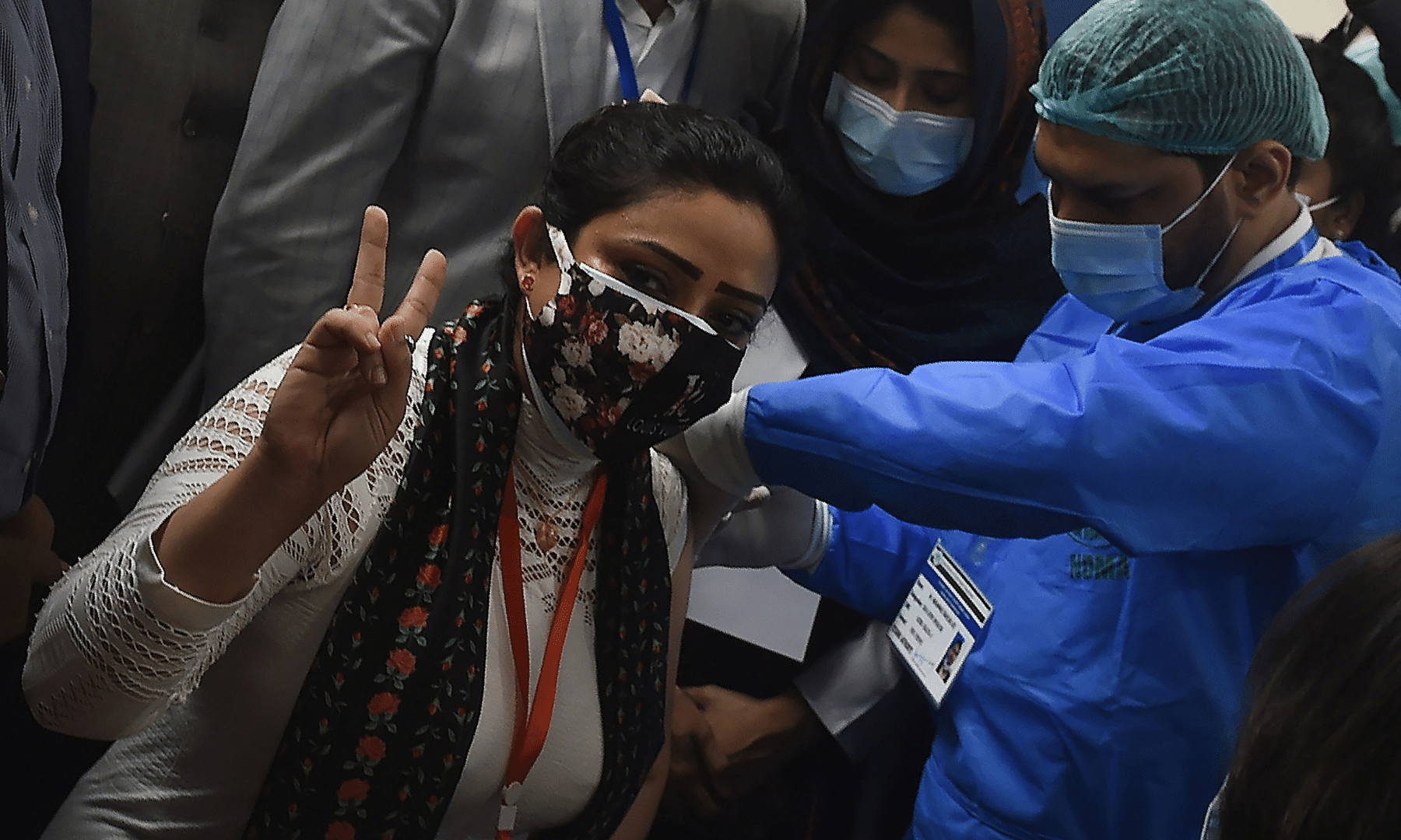 A health worker (L) gestures while receiving a dose of the Chinese-made Sinopharm Covid-19 vaccine, at a vaccination centre in Karachi. — AFP