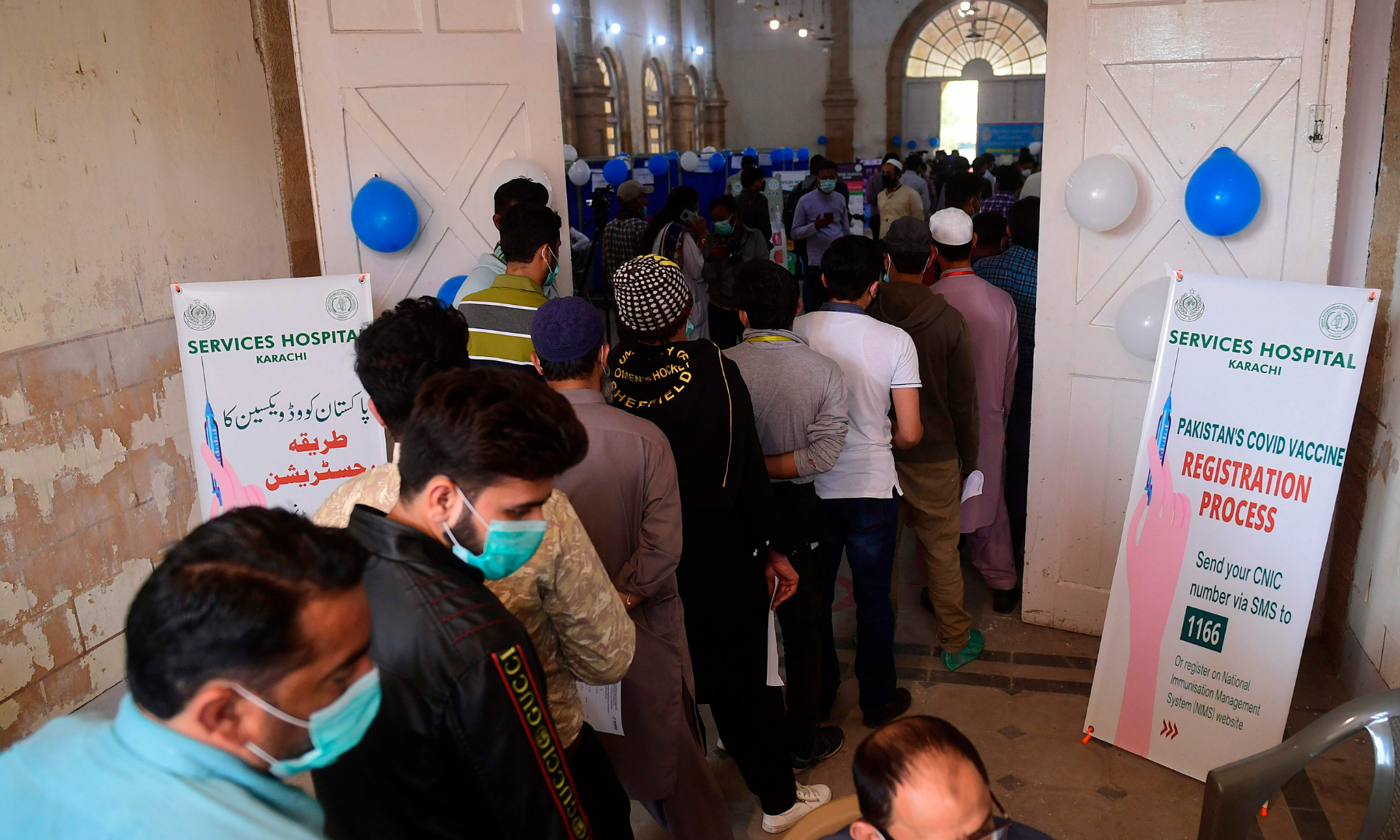 Health workers stand in a queue for their registration before receiving a dose of the Chinese-made Sinopharm Covid-19 vaccine, at a vaccination centre in Karachi. — AFP