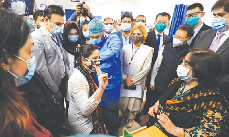 The Sindh chief minister, health minister and Chinese consul general observe as a health professional is administered the dose at the Dow University Hospital while (right) a health worker flashes his vaccination card after receiving the jab at Khaliqdina Hall on Wednesday.—Reuters/Fahim Siddiqi/White Star