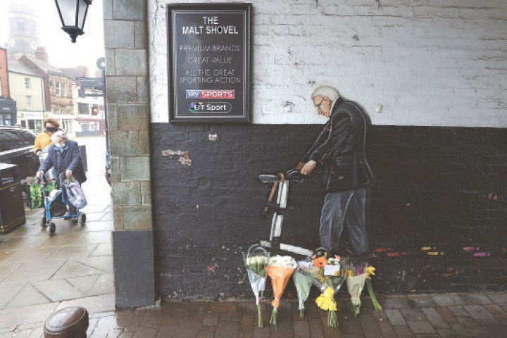 CAPTAIN Tom Moore's admirers walk beside his mural in Yorkshire.—Reuters