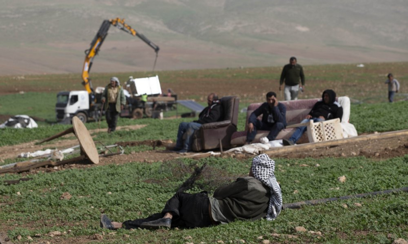 Palestinian Bedouin watch Israeli troops demolish tents and other structures of Khirbet Humsu hamlet in the Jordan Valley in the West Bank on Feb 3. — AP