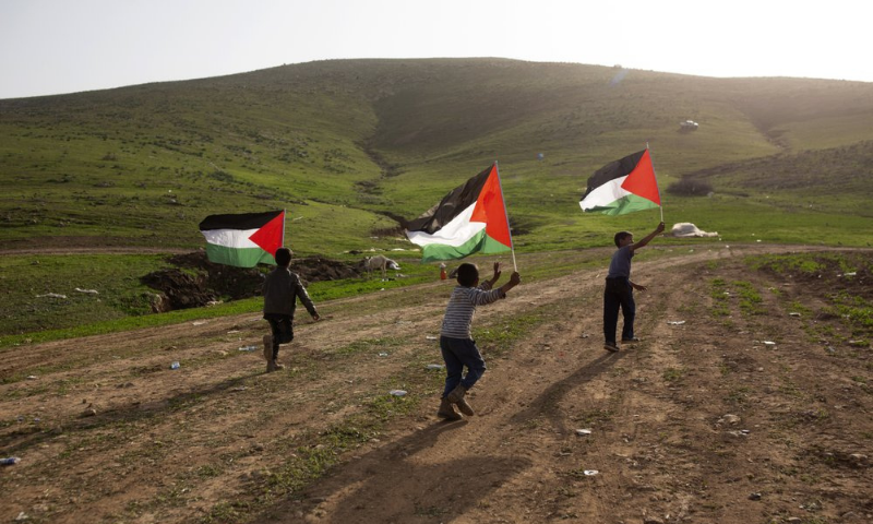 Palestinian Bedouin boys play with Palestinian flags after Israeli troops demolished tents and other structures of the Khirbet Humsu hamlet in the Jordan Valley in the West Bank on Wednesday. — AP