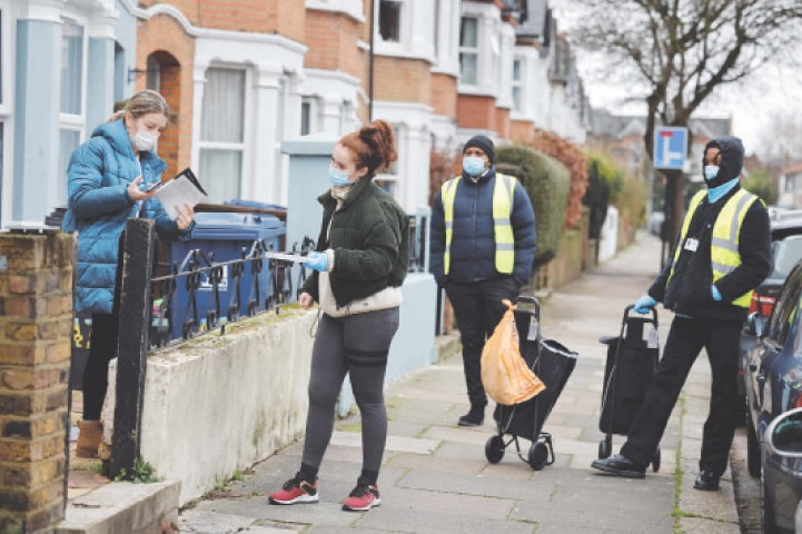 LONDON: Volunteers collect a completed Covid-19 test kit from a resident as part of testing for the new South African variant of the virus in West Ealing on Thursday. The highly transmissible variant first identified in South Africa is spreading rapidly around the world and was last week detected in the United States.—AFP