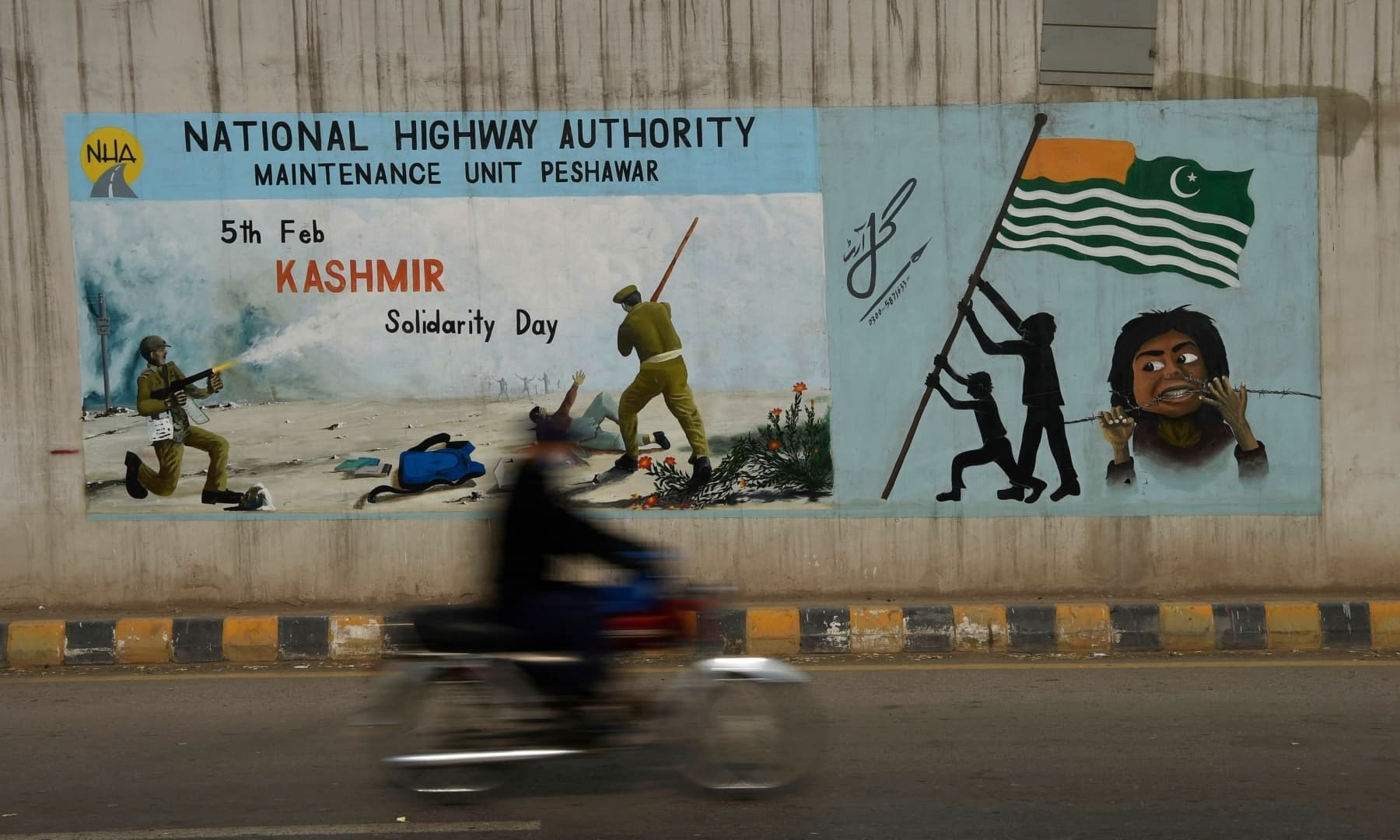 A commuter rides past a painting on a flyover depicting Kashmir Solidarity Day in Peshawar on February 5. — AFP
