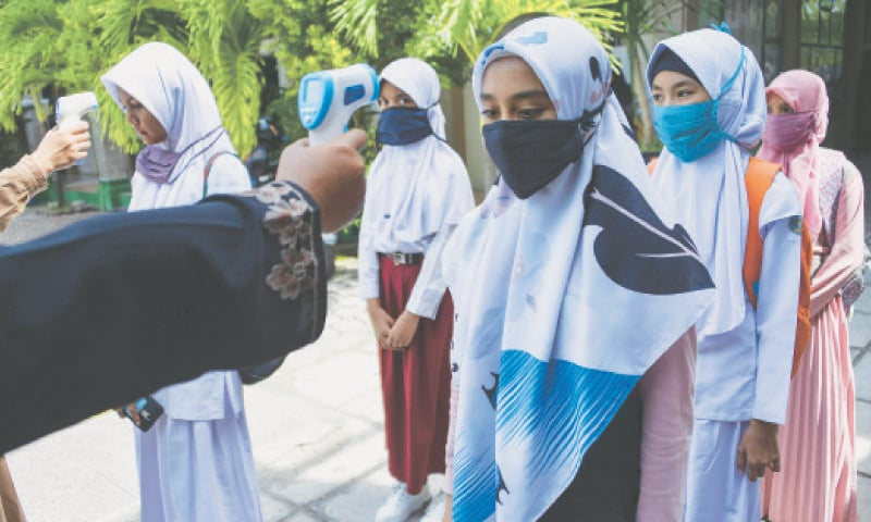 STUDENTS wearing headscarves queue up to get their temperature taken at a junior high school in Banda Aceh.—AFP
