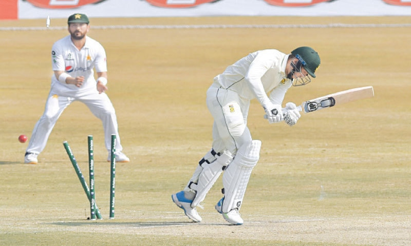 SOUTH African all-rounder George Linde is cleaned up by Pakistan fast bowler Hasan Ali during the second Test at the Rawalpindi Cricket Stadium on Saturday. (Inset) Hasan bows down to Almighty after claiming the five-wicket haul.—Tanveer Shahzad/White Star