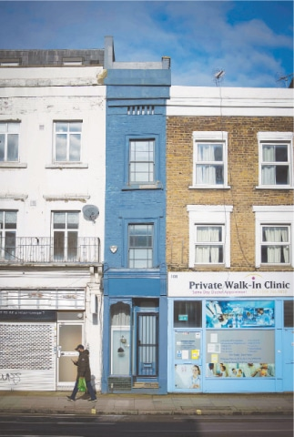 A PEDESTRIAN passes the front of 'London's thinnest house' (painted blue).—AFP