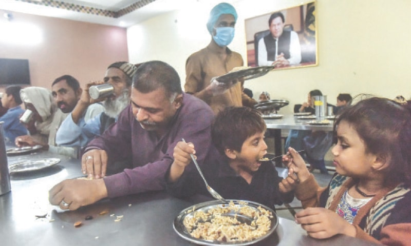 A FAMILY — a father [left] and his two children — is among many who are offered meals at Surjani Town Panahgah everyday.—Fahim Siddiqi / White  Star
