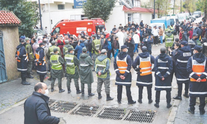 Emergency services gather at the site of an illegal underground textile workshop that flooded after heavy rainfall in Tangiers on Monday.—AFP