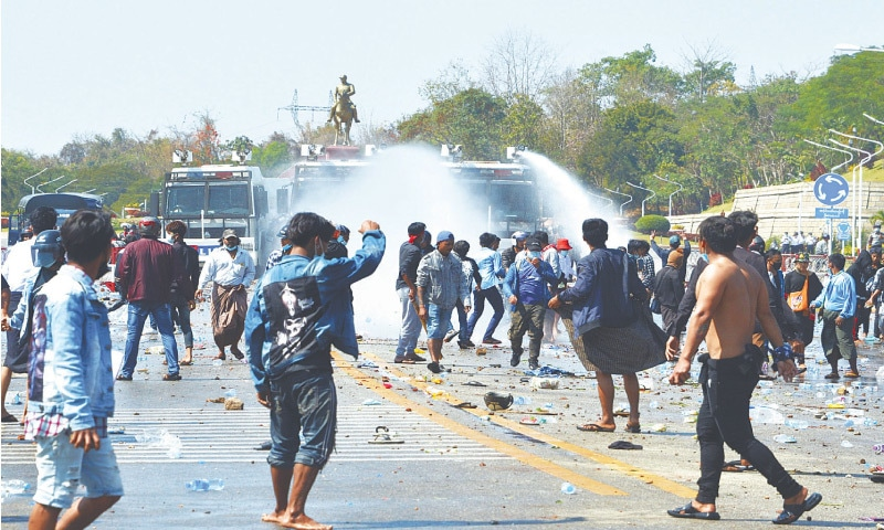 NAYPYIDAW (Myanmar): Police fire water at protesters as they demonstrate against the military coup on Tuesday. Several people were injured as police used force against the protesters.—AFP