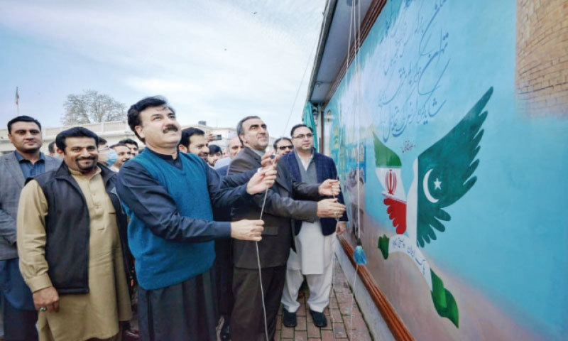 KP Minister for Culture Shaukat Yousafzai and Iranian Consul General Hamid Raza unveil a friendship wall at a ceremony in Peshawar on Wednesday. — Dawn
