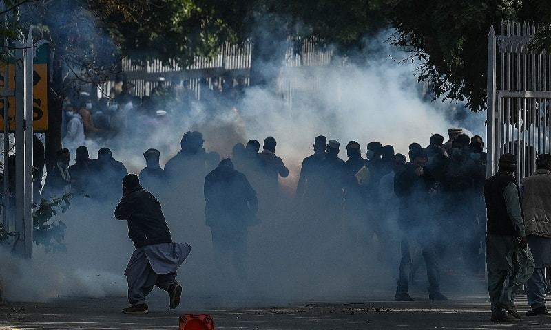 Federal government employees react as police fired teargas shells to disperse them while trying to march toward the Parliament House during a protest to demand higher wages, in Islamabad on February 10. - AFP
