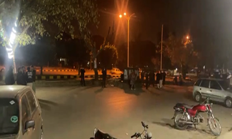 People gather outside buildings after earthquake tremors were felt in Islamabad on Friday. — DawnNewsTV