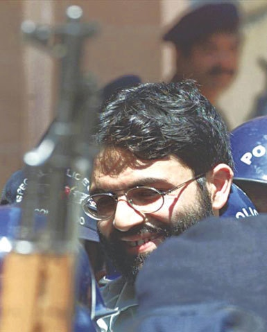 British-born Islamic militant Ahmed Omar Saeed Sheikh is surrounded by armed police as he arrives at a court in Karachi, March 29, 2002 | Reuters