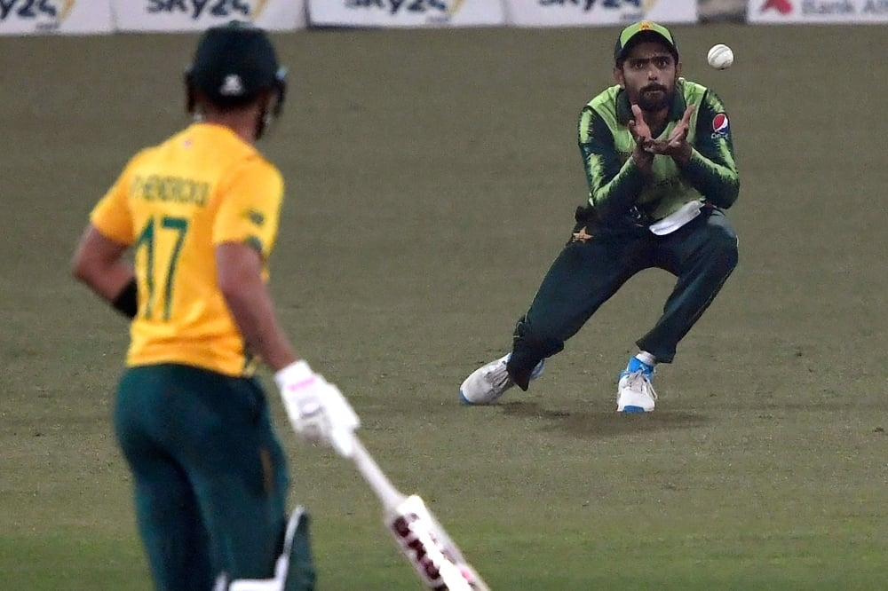 Pakistan's captain Babar Azam (R) takes a catch of South Africa's Jon-Jon Smuts (not pictured) during the second T20 international cricket match between Pakistan and South Africa at the Gaddafi Cricket Stadium in Lahore on February 13. — AFP