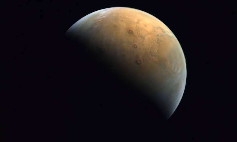 A handout picture provided on Feb 14, 2021 by the United Arab Emirates Space Agency taken by the Emirates eXploration Imager after Mars Orbit Insertion on board the First Emirates Mars Mission from an altitude of 24,700 km above the Martian surface shows the Olympus Mons, the highest volcano on Mars, and the Tharsis Montes, three volcanoes named Ascraeus Mons, Pavonis Mons and Arsia Mons. — Photo via AFP