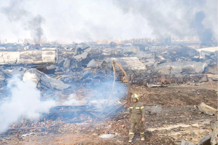 A FIREFIGHTER walks amidst wreckage of gas tankers after fire erupted at Islam Qala.—AFP