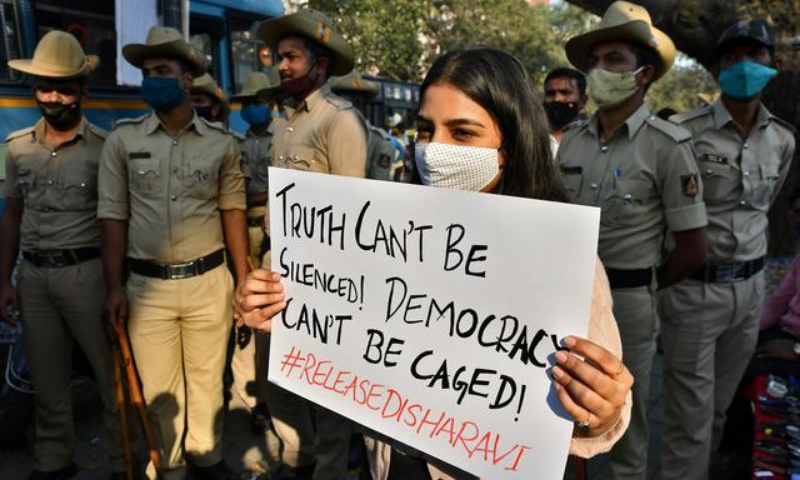 A woman holds a placard next to policemen during a protest against the arrest of climate activist Disha Ravi, in Bengaluru, India on Monday. — Reuters