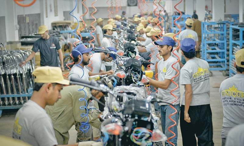 Workers assemble motorbikes at a D.S. Motors manufacturing unit in this file photo.—White Star/File photo