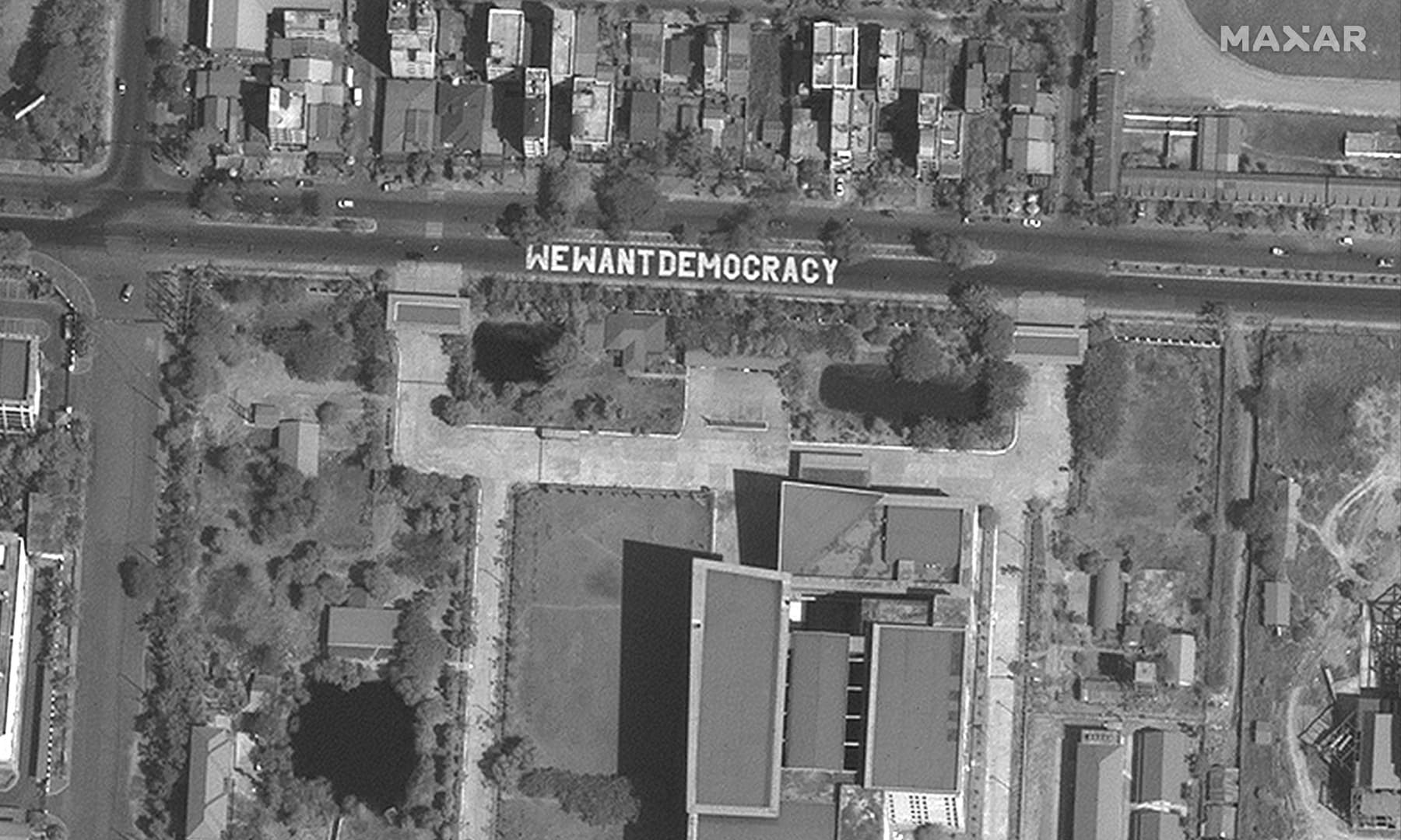 "This handout satellite image released by Maxar Technologies shows an overview of a street mural that reads ""We Want Democracy"" near the Myanmar Institute of Information, in Yangon on February 16. — AFP/Satellite image ©2021 Maxar Technologies"