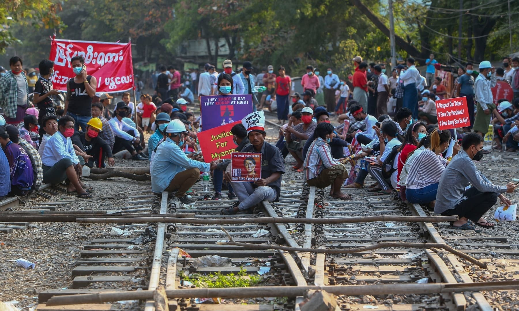 Demonstrators with placards sit on the railway tracks in an attempt to disrupt train service during a protest against the military coup in Mandalay, Myanmar on Wednesday, Feb 17. — AP